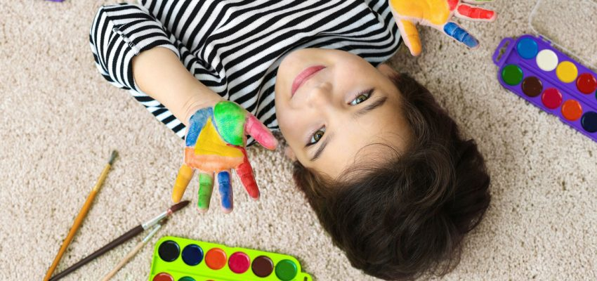 Kid laying on carpet with paint on hands