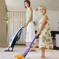 Mother and Daughter Vacuuming Carpet